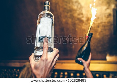 Waiter is holding bottles of vodka and champagne up at a party #602828483