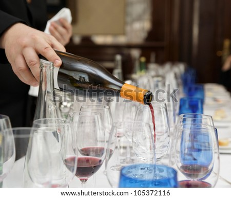 Waiter is pouring wine during a winetasting event - stock photo