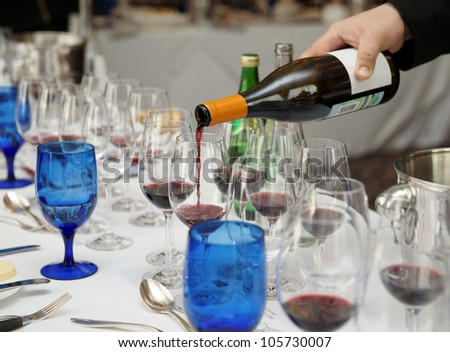 Waiter is pouring wine during a winetasting event