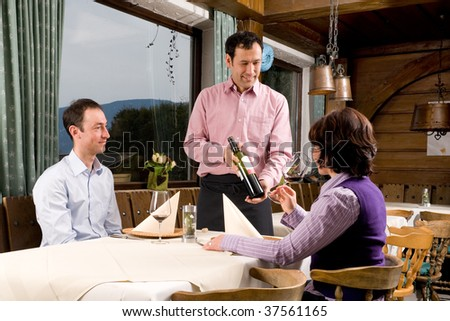 Waiter is serving some wine in a little restaurant