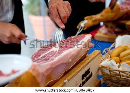 Waiter is slicing Italian raw  ham