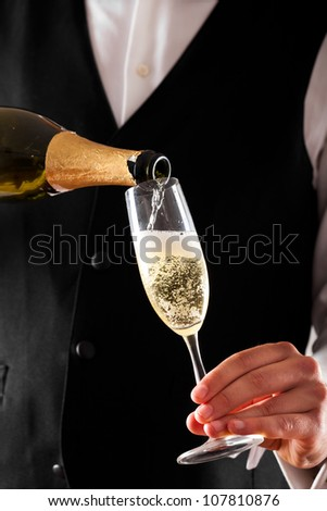 Waiter pouring champagne in a flute