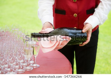 waiter pouring champagne into a flute