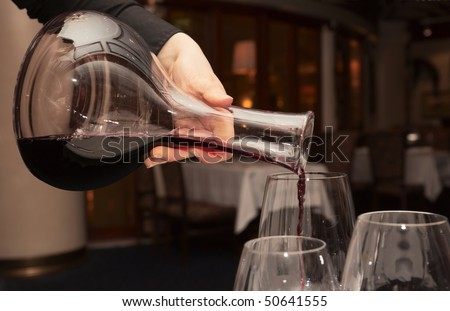 Waiter pouring red wine from decanter in dark restaurant