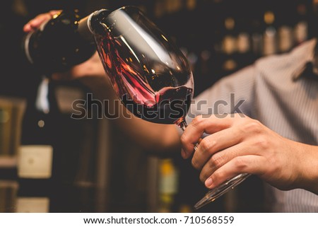 Waiter pouring red wine in a glass. #710568559