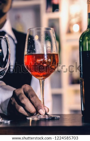 Waiter pouring red wine in a glass. on wood bar.. #1224585703