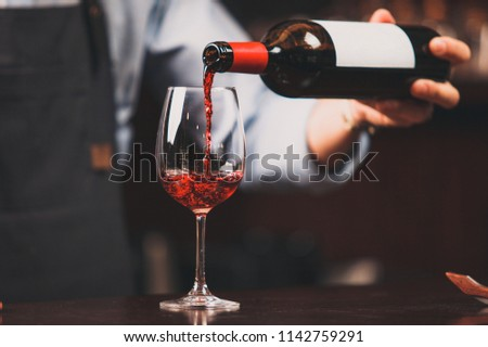 Waiter pouring red wine into wineglass #1142759291