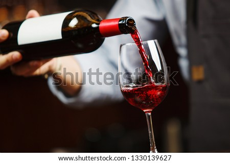 Waiter pouring red wine into wineglass. Sommelier pours alcoholic drink #1330139627
