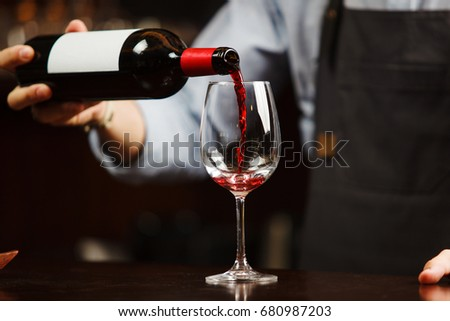 Waiter pouring red wine into wineglass. Sommelier pours alcoholic drink #680987203