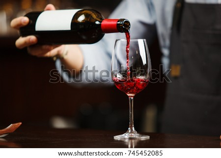 Waiter pouring red wine into wineglass. Sommelier pours alcoholic drink #745452085