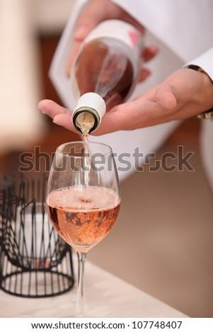 Waiter pouring sparkling wine - stock photo
