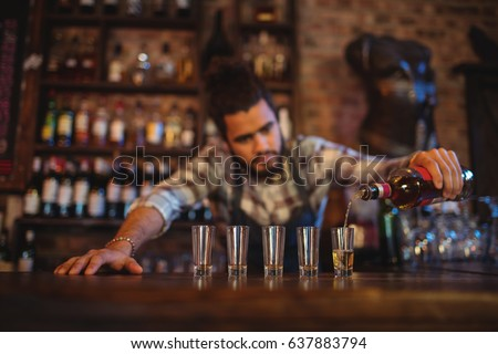 Waiter pouring tequila into shot glasses at counter in bar #637883794