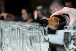 Waiter pours champagne in glasses