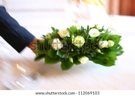 Waiter putting flowers on table. Shot with movement blur