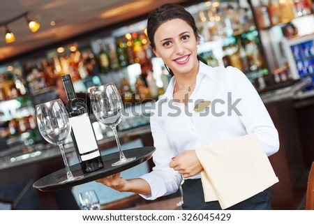 waiter restaurant catering service. Female cheerful worker with tray, glasses and bottle of wine