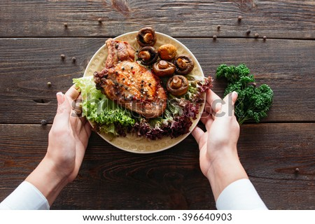 Waiter serving a chicken dish with lettuce and mushrooms. Chief decorating food for presentation in small cafe. Waiter presenting grilled chicken with salad for retail.