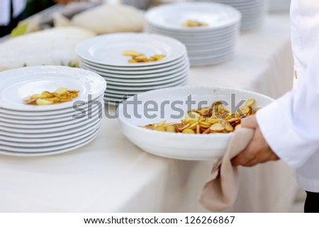 Waiter serving a large bowl of tasty fried potatoes