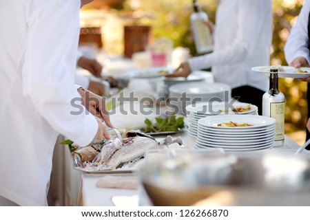 Waiter serving a tasty fish baked in salt