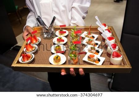 Waiter serving canape selection on slate platter