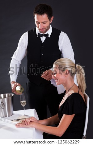 Waiter serving champagne to a beautiful blonde woman seated at a table in an elegant restaurant
