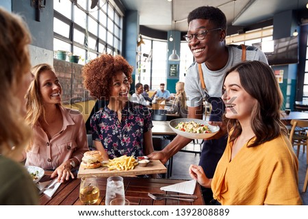 Waiter Serving Group Of Female Friends Meeting For Drinks And Food In Restaurant Foto stock ©