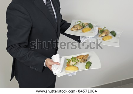 Waiter serving plates of food