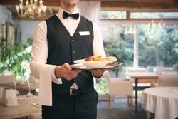 Waiter serving salad at restaurant, close up view