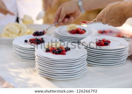 Waiter serving some plates with dessert