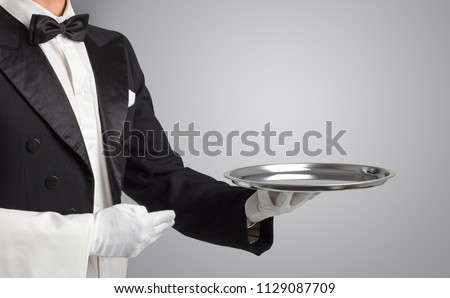 Waiter serving with white gloves and steel tray in an empty space - Shutterstock ID 1129087709