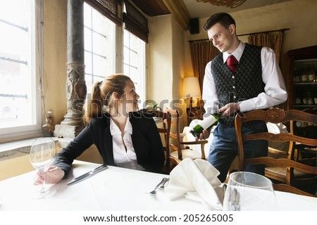 waiter showing wine bottle to...