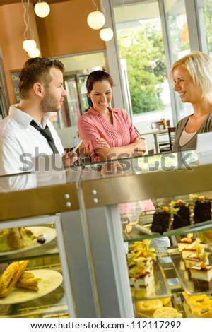 Waiter showing women cakes on window display cafe smiling friends