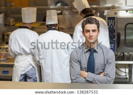 Waiter standing in a busy kitchen with three chefs behind him
