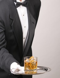 Waiter wearing a tuxedo leaning in to serve a glass of whiskey on a silver tray. Vertical format showing the mans torso only over a gray background with copy space.