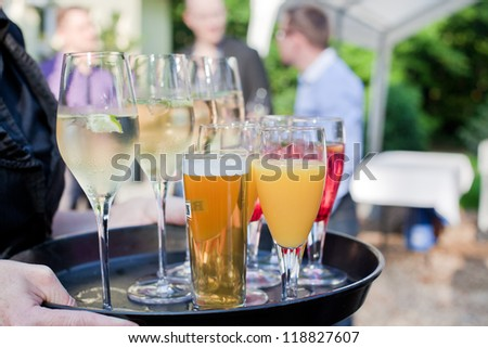 Waiter with dish of champagne, cocktails, beer and juice glasses