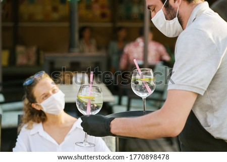 Waiter with gloves and medical facemask keeping social distance with customer in restaurant. Aftermath of covid-19 relief of quarantine measures