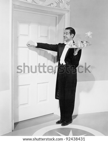 Waiter with tray knocking on a door