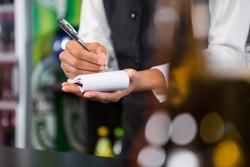 Waiter writing down an order in a bar