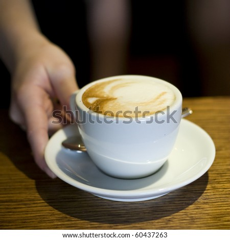 waiters hand gives cappuccino