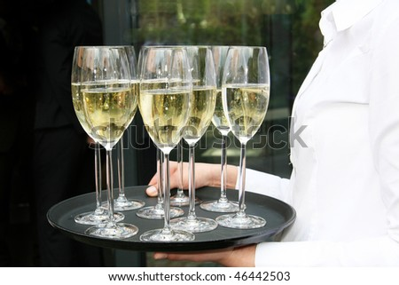 Waiters served champagne glasses on a tray.