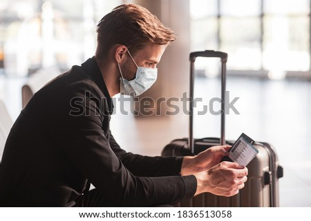 Waiting for a flight. A man wearing a face mask while waiting for a flight