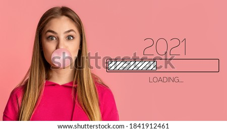 Waiting For 2021 New Year. Happy Millennial Woman Blowing Bubble Gum, Awaiting Upcoming 2021 Loading Process Bar, Posing Looking At Camera On Pink Background. New Year Coming Soon. Panorama