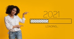 Waiting For 2021 New Year. Joyful Black Woman Pointing Finger At 2021 Loading Process Bar Standing Over Yellow Background. Anticipation, Awaiting Upcoming Better Year Concept. Panorama