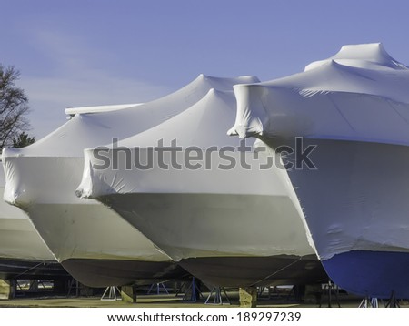 Waiting for nice weather is part of a lifestyle: Bows of shrink-wrapped yachts in boatyard on a sunny morning, spring in southwestern Michigan