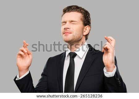 Waiting for special moment. Portrait of young man in formalwear keeping fingers crossed and eyes closed while standing against grey background