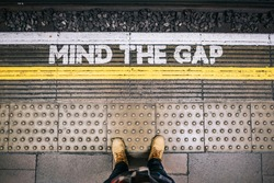 Waiting for the subway train at the station from the platform seeing the Mind the Gap letters