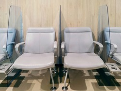 Waiting lounge armchair with clear acrylic shield stand between gaps of seating in lobby public area for preventing virus outbreak. New normal preventive measure in pandemic situation.