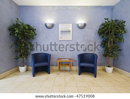 waiting room with blue armchairs and plants