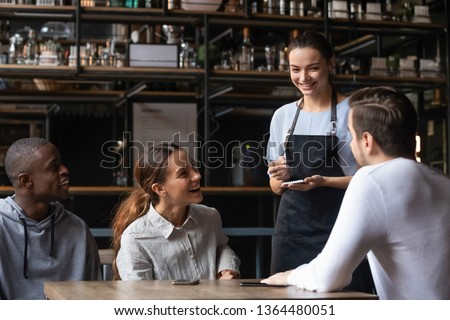 Waiting staff in apron holds notepad ready take order restaurant visitors advises dishes and drinks to diverse cheerful friends, restaurant business, eating outside the home weekend activities concept