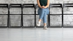 Waiting time. Cropped view of young female job applicant or public officer visitor sitting cross legged on chair in corridor close to hr or functionary office showing confidence patience, copy space
