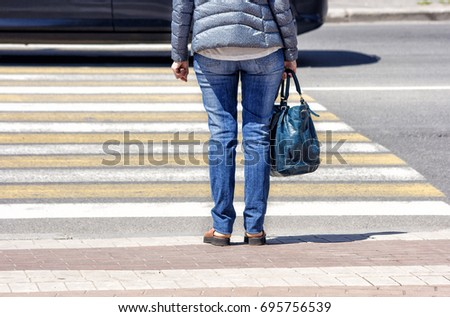 waiting woman at the pedestrian crossing and car traffic on sunny summer day #695756539